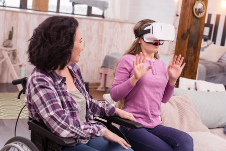 VR universe. Disabled woman looking at amazed girl who wearing VR glasses