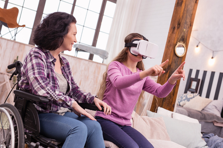 VR with family. Pleasant disabled woman staring at girl who wearing VR headset Stock Photo