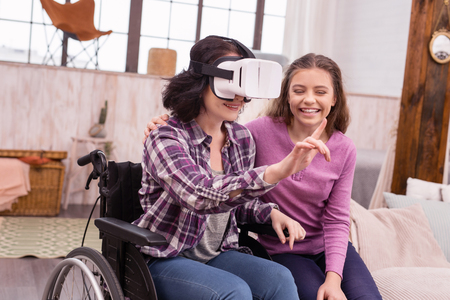 Virtual reality. Glad disabled woman wearing VR glasses while girl laughing Stock Photo