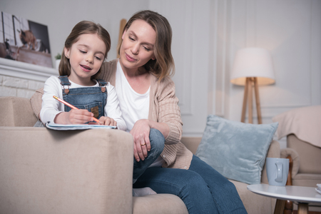 Learning process. Inspired little girl sitting on the couch with her mother and writing Stock Photo