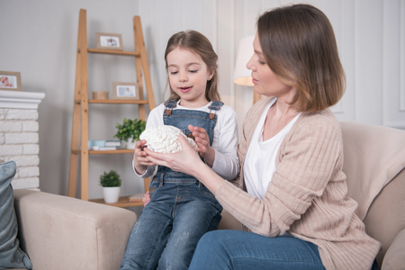 How interesting. Happy fair-haired girl holing artificial brains and sitting on the sofa with her mom