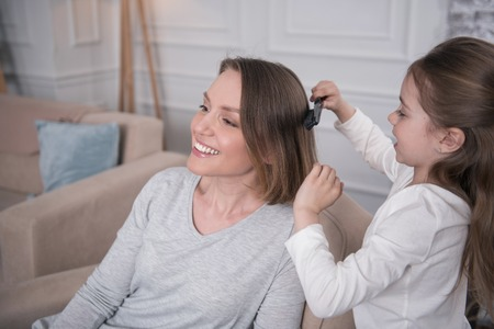 I cherish you. Pretty cheerful mother smiling and her daughter combing her hair