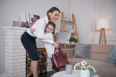 À plus. Charmante fille joyeuse souriant et serrant sa mère