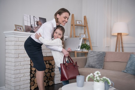 See you. Charming cheerful girl smiling and hugging her mom Stock Photo