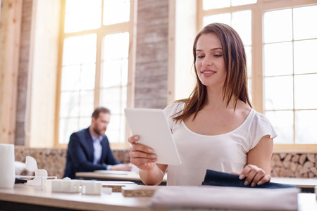 Online technology. Musing reflective businesswoman using tablet while posing at table Stock Photo