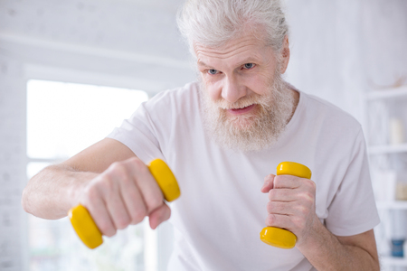 I love boxing. The close up of a handsome elderly man in a white t-shirt practicing boxing kicks while working out in the morning Stok Fotoğraf