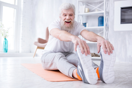 Stretching muscles. Pleasant elderly man sitting on the yoga mat, tugging at his toes and smiling widely, being happy about his suppleness