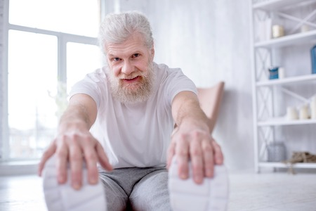 In great mood. Handsome senior man sitting on the floor in the living room and smiling at the camera while bending forward and touching his toes Stock Photo