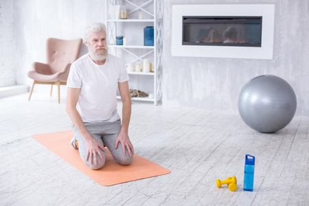 Preparing for workout. Bearded senior man standing on his knees on the yoga mat before proceeding to his morning calisthenics