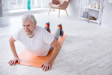 Strengthening back. Charming elderly man lying on the yoga mat and arching his back while doing stretching exercises Stock Photo