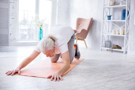 Enjoying yoga. White-haired senior man standing in an extended puppy pose while practicing yoga in the morning at home