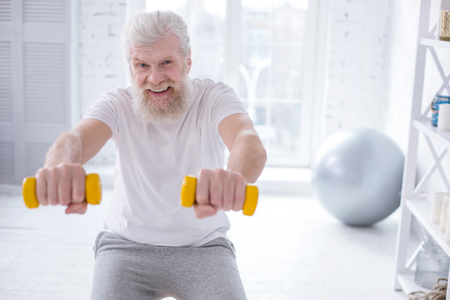 Generating endorphins. Upbeat elderly man grinning while exercising with dumbbells and doing squats