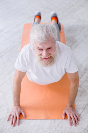 Yoga enthusiast. The top view of a handsome elderly man smiling pleasantly while standing in upward-facing dog pose on a yoga mat Stock Photo