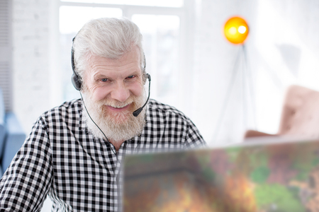 Love gaming. Cheerful elderly man smiling at the camera while playing a video game online and discussing strategy with his friends through video call
