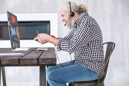Interesting gameplay. The side view of a grey-haired senior man sitting at the table and playing a battle simulator, being fully immersed into the game