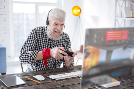 Great gaming experience. Upbeat elderly man being excited while playing a multiplayer online video game with a controller Foto de archivo