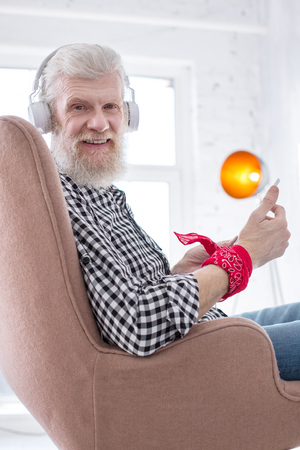 Cheering himself up. Pleasant senior man sitting in an armchair and smiling at the camera while using a tablet and listening to the music Foto de archivo
