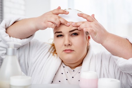 Problem-prone skin. Concentrated overweight woman wearing a bathrobe and popping pimples