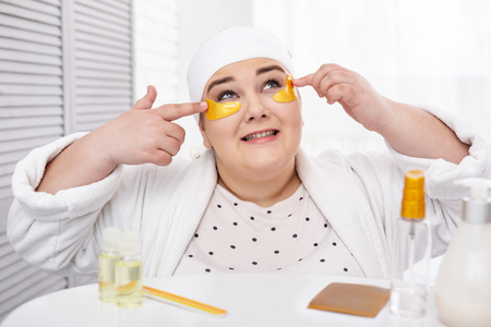 Staying beautiful. Inspired overweight woman wearing a bathrobe and making an eye mask Stock Photo