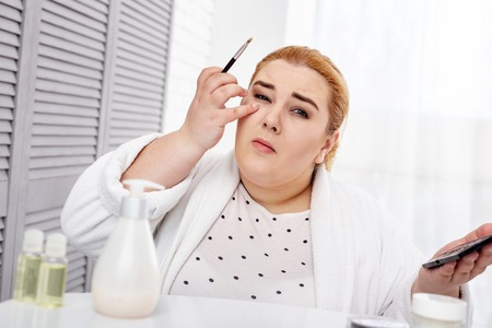 Determination. Concentrated fat woman wearing a bathrobe and applying make-up