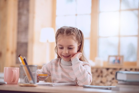 Home education. Cute smart girl smiling while studying at home Stock Photo