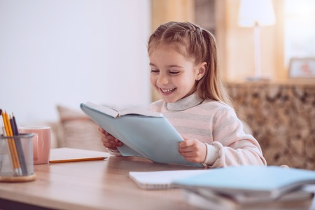 Interesting subject. Happy smart girl holding a textbook while reading it