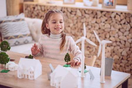 Eco housing. Positive cute girl looking at the windmill models while playing at home