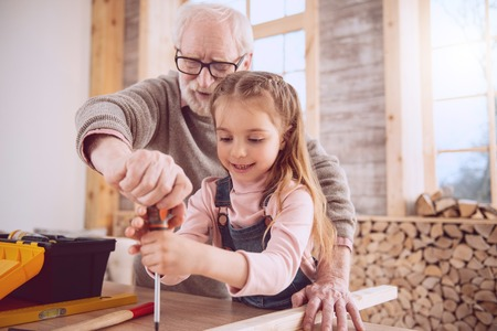 Positive cheerful man holding a screwdriver while working together with his granddaughter in the workshop