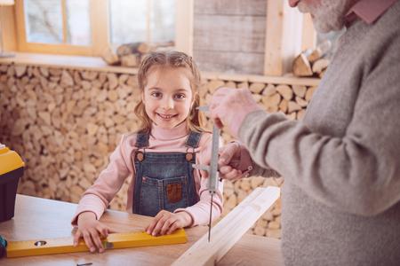Joyful nice girl smiling to you while enjoying being in the workshop Stock Photo