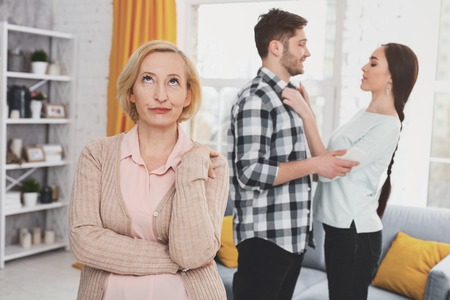 Unhappy aged woman standing in the living room while thinking about her daughters husband Stock Photo