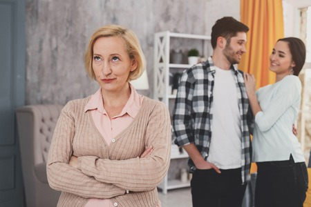 Unpleased mother in law folding her hands while expressign her negative attitude
