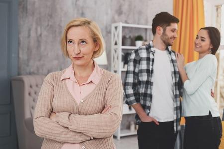 Unzufriedene Schwiegermutter faltet die Hände und drückt gleichzeitig ihre negative Einstellung aus Standard-Bild - 102188350