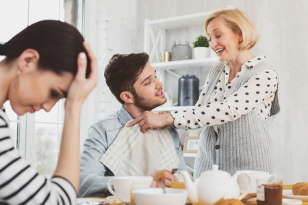 Cheerful positive woman smiling to her son while being too caring for him Stock Photo