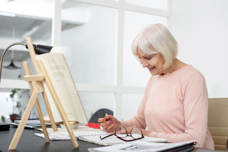 Pleased senior woman studying while making records