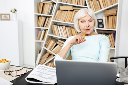 Serious senior freelancer using laptop while biting pencil Фото со стока