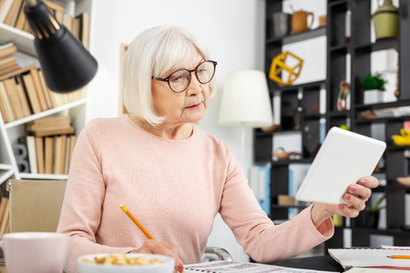 Beautiful senior woman using tablet while noting Stock Photo