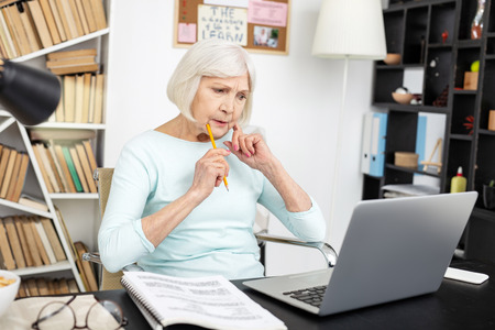 Uneasy senior freelancer using laptop while touching face