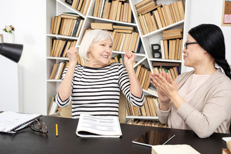 Jovial senior woman smiling while tutor clapping