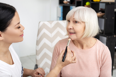Satisfied volunteer and senior woman using foundation while talking Stock Photo