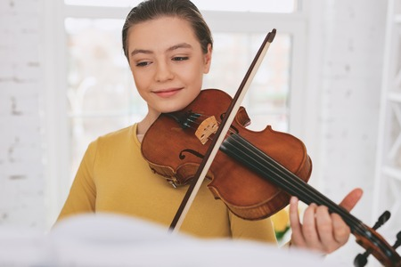 Pretty young female keeping smile on her face while playing the violin