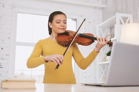 Attentive girl keeping back straight while playing the violin Stock Photo