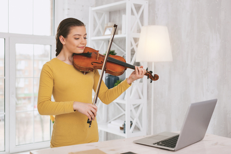 Pretty brunette holding violin while watching video lesson Reklamní fotografie - 101477405