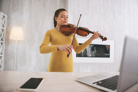 Attentive young female using her instrument while learning classical work Stock Photo