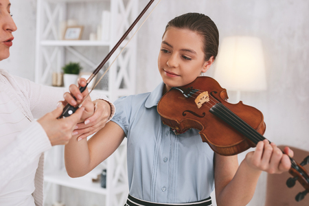 Attractive young female holding violin while going to play favorite melody