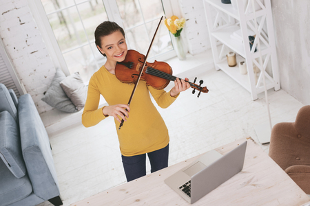 Happy young female using her violin while playing classical melody Stock Photo