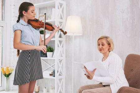 Conscious brunette girl holding violin while playing new song