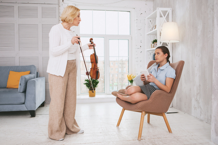 Relaxed girl holding tablet in both hands while having conflict with her mom