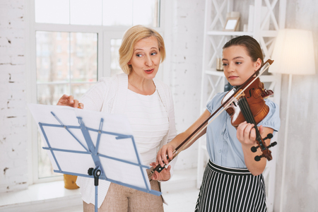 Conscious girl looking forward while playing the violin Stock Photo