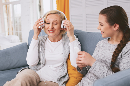 Pleased female keeping smile on her face while listening favorite song Stock Photo