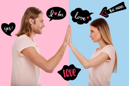 Waist up of young cheerful couple standing in front of each other while giving five and expressing love Stock Photo